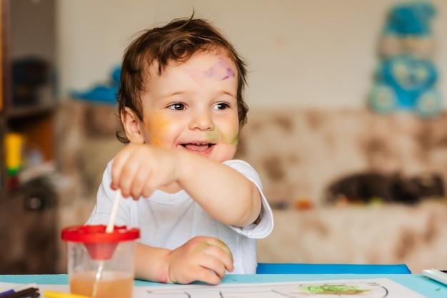 Menino bonitinho desenha com pincéis e tintas coloridas em uma folha de papel