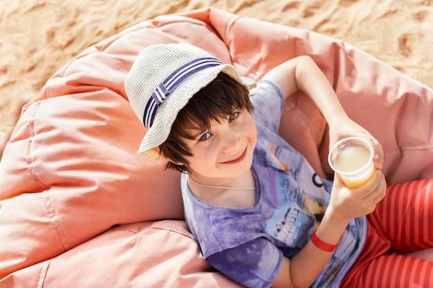 Menino bonitinho desfrutando de juce durante as férias tropicais à beira-mar. adorável criança bebe coquetel saboroso com prazer, sentado em uma aconchegante poltrona de lixo em um dia quente na praia.