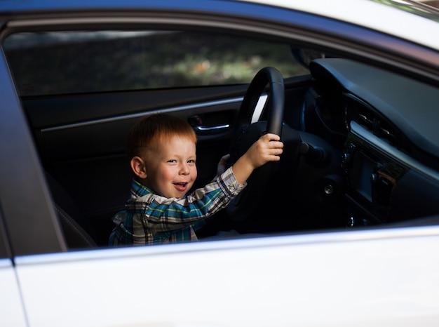 Menino bonitinho dirigindo carro de pais