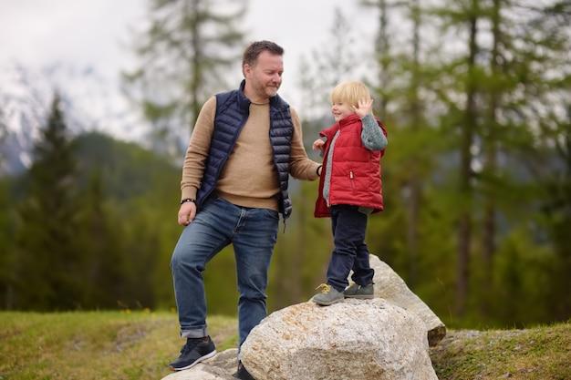Menino bonitinho e seu pai caminha no parque nacional suíço na primavera.