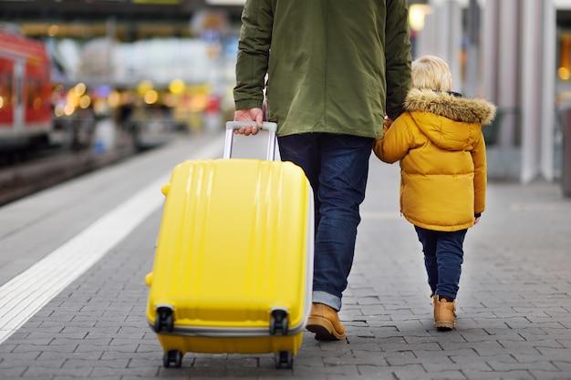 Menino bonitinho e seu pai esperando trem expresso na plataforma da estação ferroviária