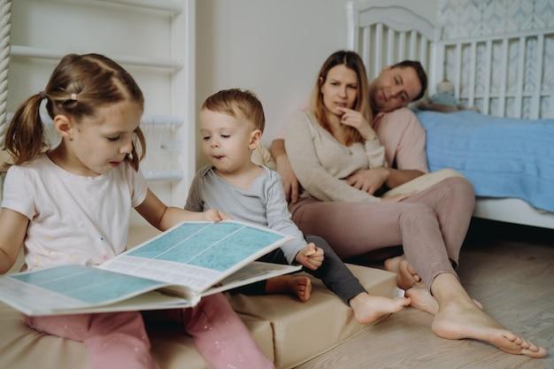 Menino bonitinho e um menino lendo livro no quarto de criança jovens pais no fundo, sentado no floo.