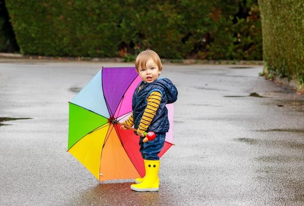Menino bonitinho em borracha amarela botas com guarda-chuva colorido arco-íris, ficar na estrada molhada