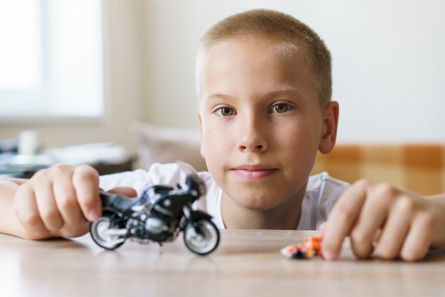Menino bonitinho em idade escolar de aparência europeia se senta na cadeira à mesa e brinca com um brinquedo ...