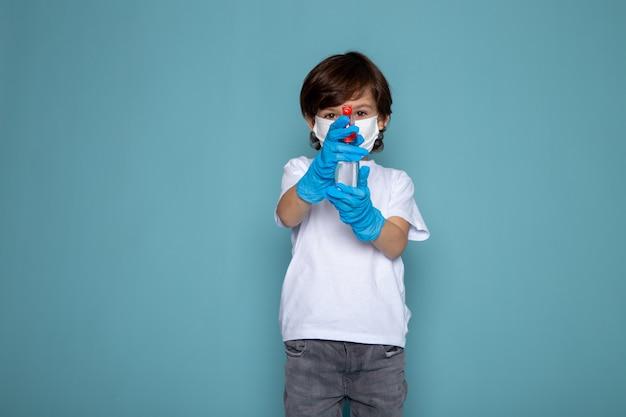 Menino bonitinho em luvas azuis e máscara protetora estéril branca usando spray na parede azul