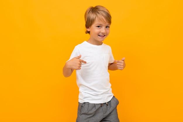 Menino bonitinho em t-shirt e calças sorri e mostra-se isolado em amarelo