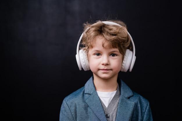 Menino bonitinho em trajes casuais ouvindo música em fones de ouvido brancos na frente da câmera sobre o espaço negro