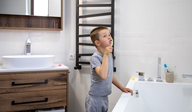 Menino bonitinho escovando os dentes no interior de um banheiro aconchegante.