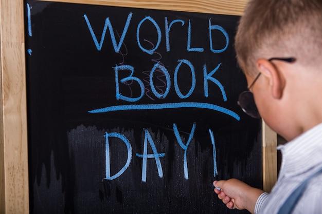 Menino bonitinho escrevendo na sala de aula. feliz dia internacional do livro mundial.