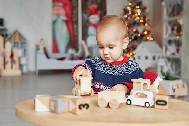Menino bonitinho está brincando com o trem de brinquedo de madeira, carro de brinquedo, pirâmide e cubos, aprendendo o conceito de desenvolvimento. desenvolvimento de habilidades motoras finas para crianças, imaginação e pensamento lógico