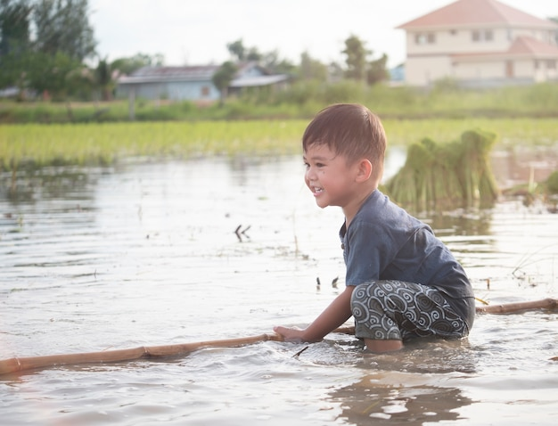 Menino bonitinho está brincando em campos de arroz lamacentos.