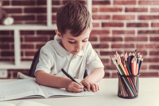 Menino bonitinho está escrevendo e sorrindo enquanto estiver jogando em casa