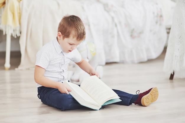 Menino bonitinho está indo para a escola pela primeira vez. criança com mochila e livro. garoto faz uma maleta, quarto de criança em um plano de fundo. de volta à escola