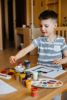 Menino bonitinho está jogando e pintando no quarto dele. recreação e entretenimento.