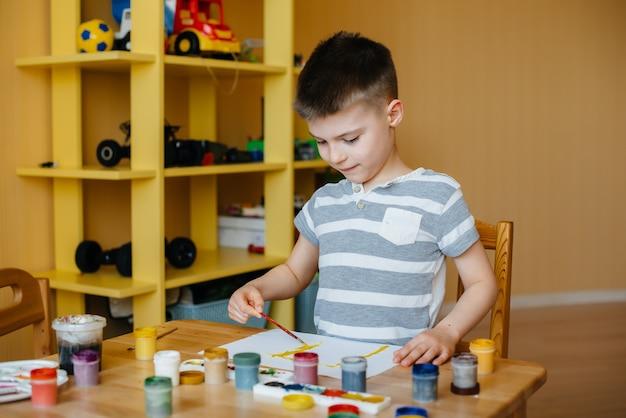 Menino bonitinho está jogando e pintando no quarto dele.