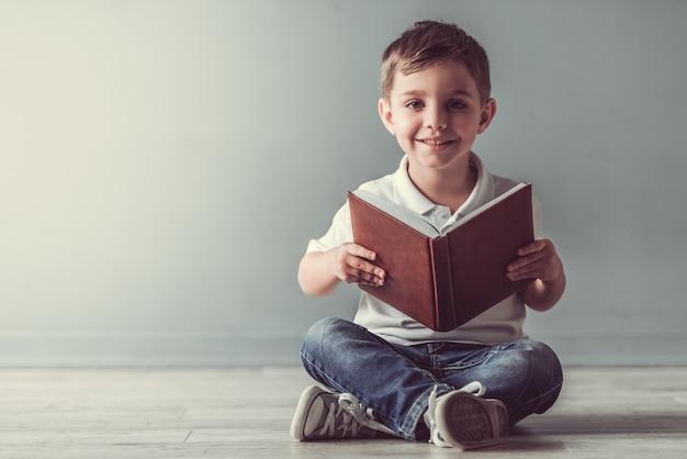 Menino bonitinho está segurando um livro, olhando para a câmera.