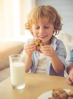 Menino bonitinho está sorrindo, bebendo leite e comendo biscoitos