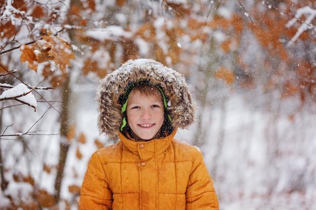 Menino bonitinho, garoto com roupas de inverno, caminhando sob a neve