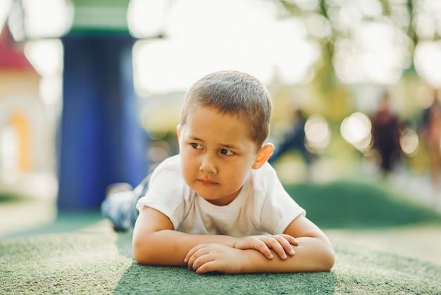 Menino bonitinho hasfun em um playground