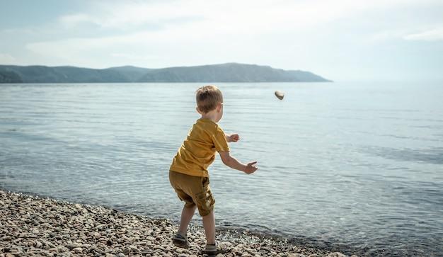 Menino bonitinho jogando pedras na água na margem de um grande lago