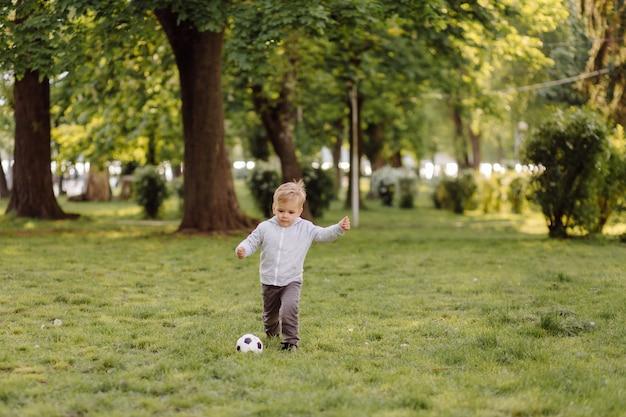 Menino bonitinho jogar uma bola de futebol ao ar livre
