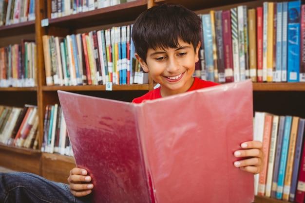 Menino bonitinho lendo livro na biblioteca
