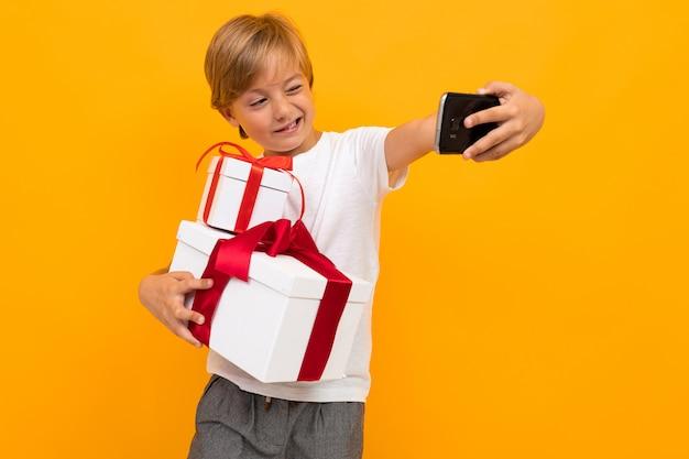 Menino bonitinho na camiseta e calça segura uma caixa com presente próprio isolado em fundo amarelo