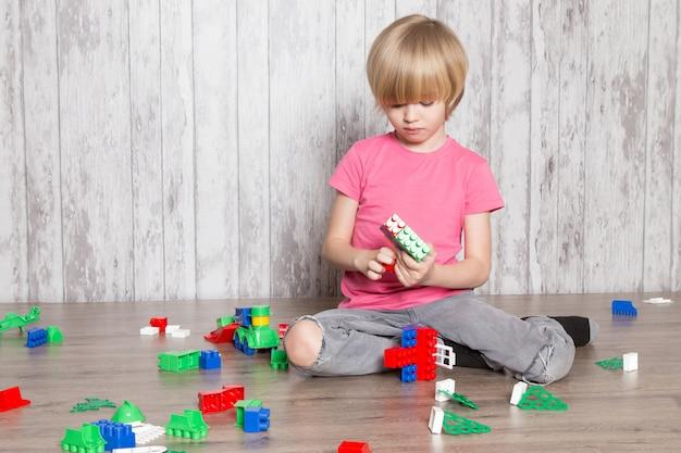 Menino bonitinho na camiseta rosa e calça jeans cinza, brincando com brinquedos