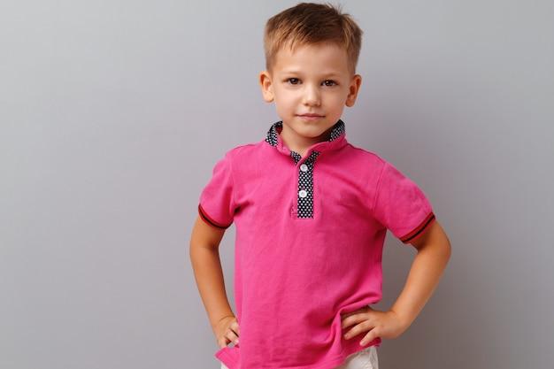 Menino bonitinho na camiseta rosa posando contra fundo cinza