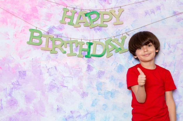 Menino bonitinho na camiseta vermelha, decorar a parede colorida com palavras de feliz aniversário