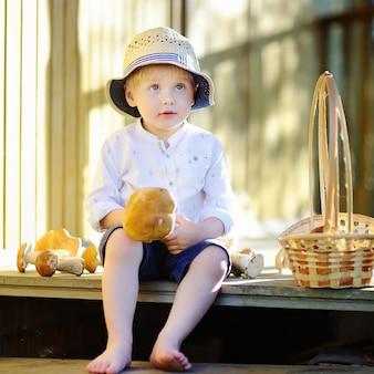 Menino bonitinho no chapéu de palha colhendo cogumelos