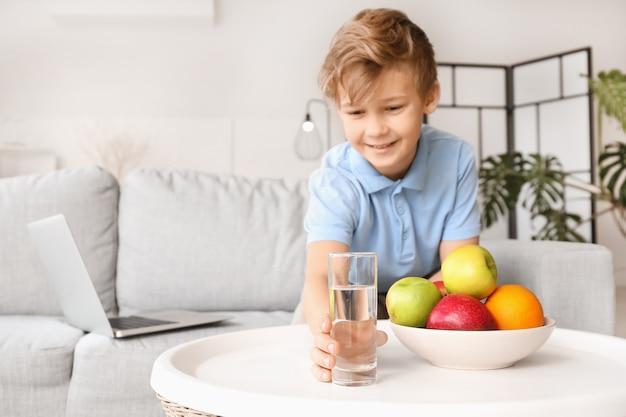 Menino bonitinho pegando um copo d'água da mesa em casa