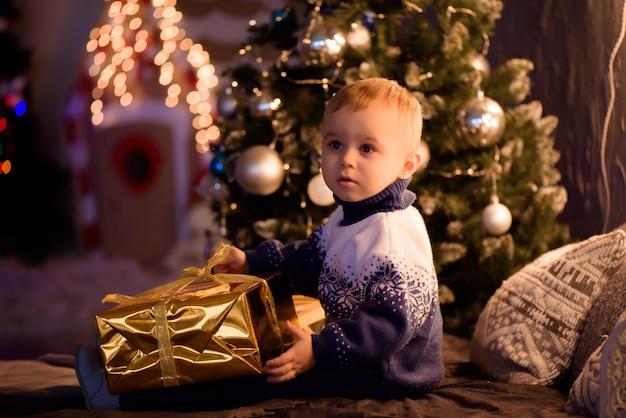 Menino bonitinho perto de sua casa decorada para o natal. feliz natal e feliz ano novo.