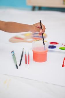 Menino bonitinho pintura no chão em sala de aula