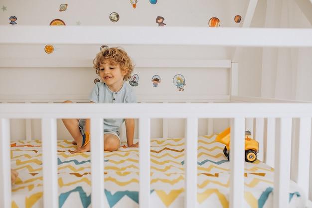 Menino bonitinho se divertindo na cama em forma de uma casa