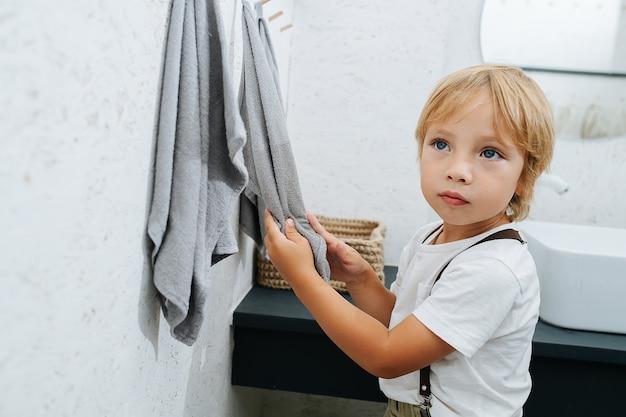 Menino bonitinho secando as mãos na vista lateral do banheiro