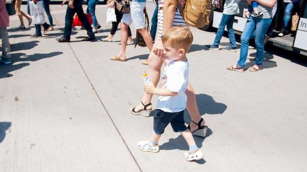 Menino bonitinho segurando a mão das mães e saindo do ônibus no aeroporto.