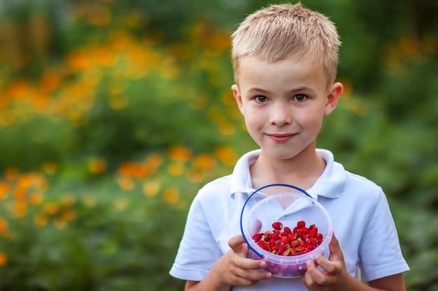 Menino bonitinho segurando a tigela com morangos