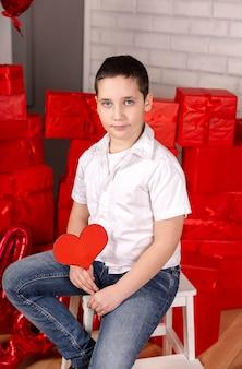 Menino bonitinho segurando coração menino com um coração dia dos namorados