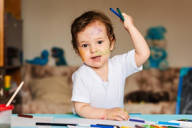 Menino bonitinho segurando lápis de cor e marcadores