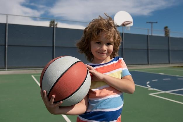 Menino bonitinho segurando uma bola de basquete tentando fazer um esporte de pontuação para crianças