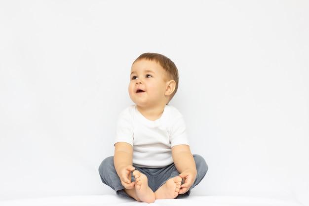 Menino bonitinho sentado isolado no fundo branco. olhando o conceito.