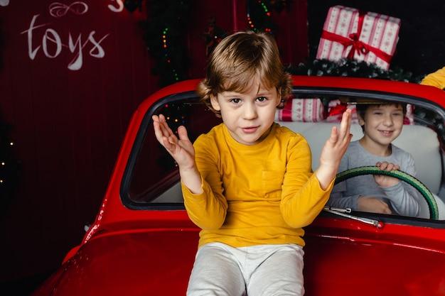 Menino bonitinho sentado no carro vermelho de natal. criança. espírito de natal. feriados.