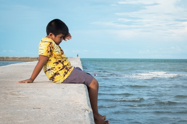 Menino bonitinho sentado sozinho na passarela no mar