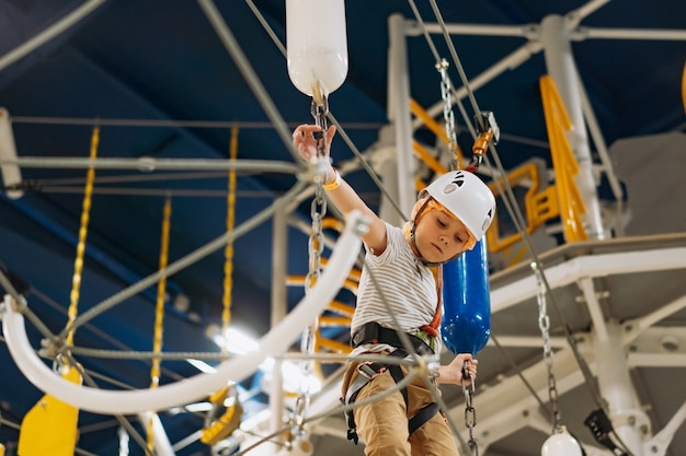 Menino bonitinho subindo no parque de aventura, passando pela pista de obstáculos. parque de corda alta dentro de casa