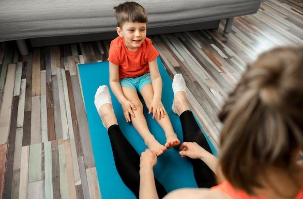 Menino bonitinho treinando com a mãe em casa