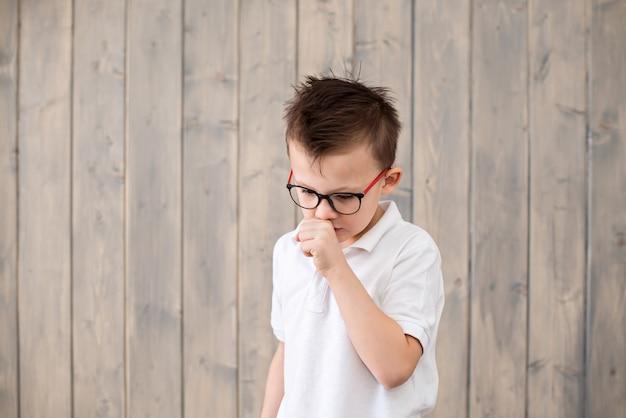 Menino bonitinho usando óculos, tossindo, na superfície de madeira marrom