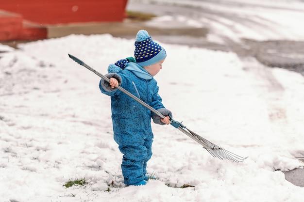 Menino bonitinho vestido com roupas de inverno azul brincando com garfo de feno na neve.
