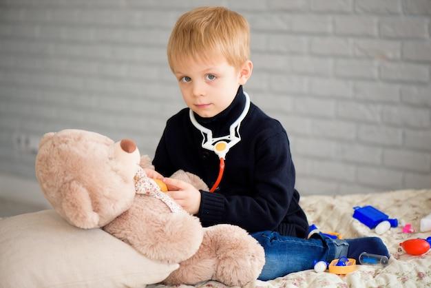 Menino bonitinho vestido como médico brincando com urso de brinquedo em casa.