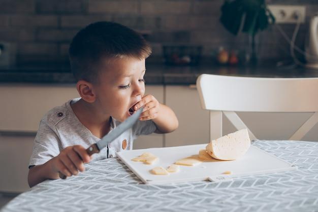 Menino bonito, 4-5 anos de idade com uma faca de cortar um queijo na tábua sobre a mesa na cozinha